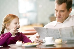Father reading paper at cafe with his little daughter