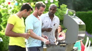 stock-footage-three-men-cooking-on-barbecue-and-toasting-beer-bottles-in-backyard